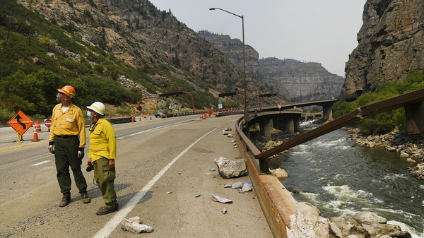 Great Basin National Incident Management One Team Public Information Officers Wayne Patterson, left, and Mike Ferris, center, check out rock fall that fell from high cliffs causing damage onto I-70 below making it dangerous for passing vehicles during the Grizzly Creek Fire in Glenwood Canyon on August 17, 2020 near Glenwood Springs, Colorado.