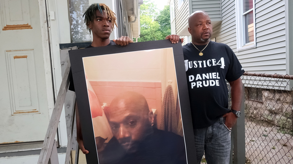 """Family members Armin Prude (left) and Joe Prude stand with a picture of Daniel Prude in Rochester, N.Y., Thursday, Sept. 3, 2020. While suffering a mental health crisis, Prude, 41, suffocated after police in Rochester put a """"spit hood"""" over his head while being taken into custody. He died March 30 after he was taken off life support, seven days after the encounter with police."""