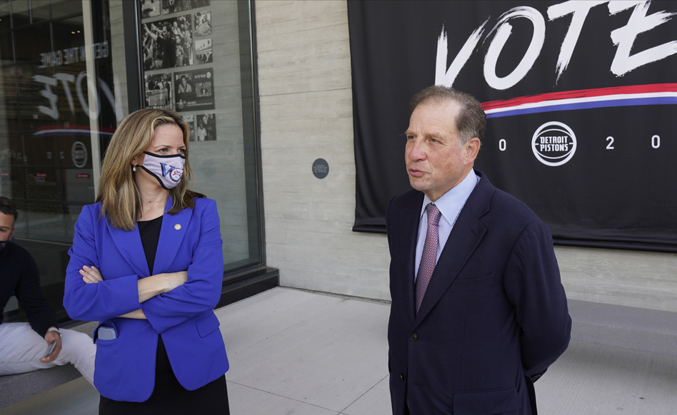 Michigan Secretary of State Jocelyn Benson (left) and Detroit Pistons Vice Chairman Arn Tellem talk about voting last Thursday, when balloting began in the state. The Pistons are allowing their arena to be used as a polling station. (Paul Sancya/AP)