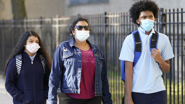 A mother accompanies her children as they arrive for the first day of in-person classes at Erasmus High School in Brooklyn