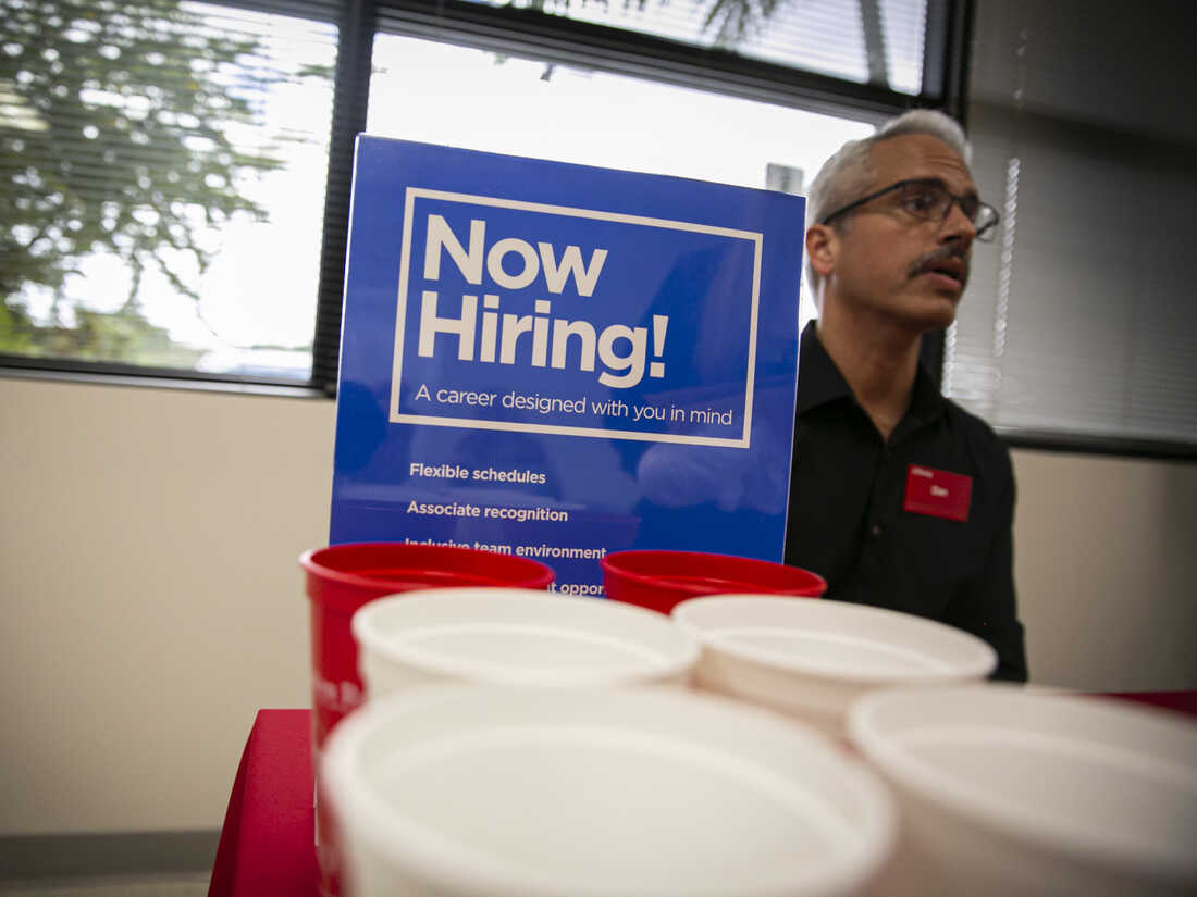 """A """"Now Hiring"""" sign is displayed during a job fair for Hispanic professionals in Miami, Florida."""