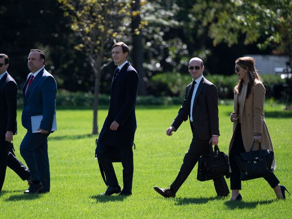 Hope Hicks and other White House staffers walk to Marine One to depart from the South Lawn of the White House on Wednesday.