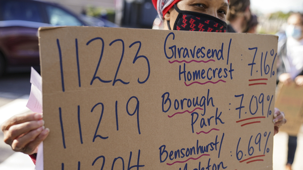 Teachers and staff protest outside Franklin D. Roosevelt High School as they call for more and better COVID-19 testing and precautions on Friday in New York City. The ZIP codes listed on this sign are among those soon to face restrictions by the city.