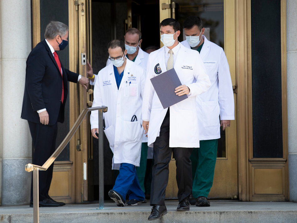 White House chief of staff Mark Meadows holds the door for Dr. Sean Conley and other members of the president's medical team on Sunday. Another update on Trump's condition is expected sometime on Monday. (Brendan Smialowski/AFP via Getty Images)