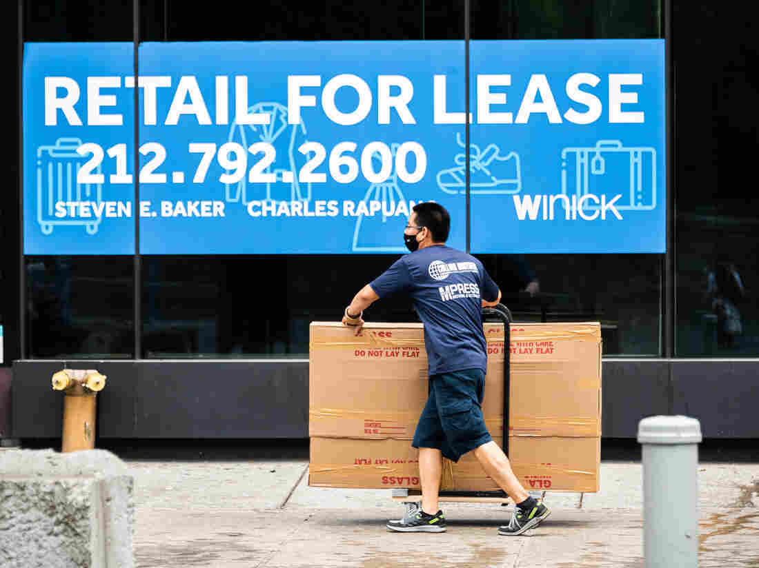 NEW YORK, NEW YORK - SEPTEMBER 29: A mover walks past a vacant store in Union Square as the city continues Phase 4 of re-opening following restrictions.