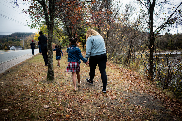 Vanessa Shefer (right) walks with her family along the Passumpsic River in St. Johnsbury, Vt.