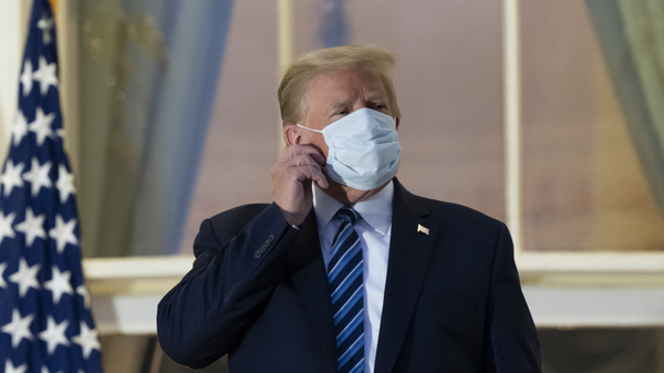 President Trump removes his mask as he stands on the Blue Room Balcony upon returning to the White House on Monday after undergoing treatment for COVID-19 at Walter Reed National Military Medical Center, in Bethesda, Md.