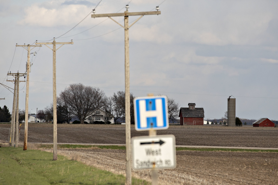 A road sign for a nearby hospital along a rural road outside Sandwich, Ill., in April. (Daniel Acker/Bloomberg via Getty Images)