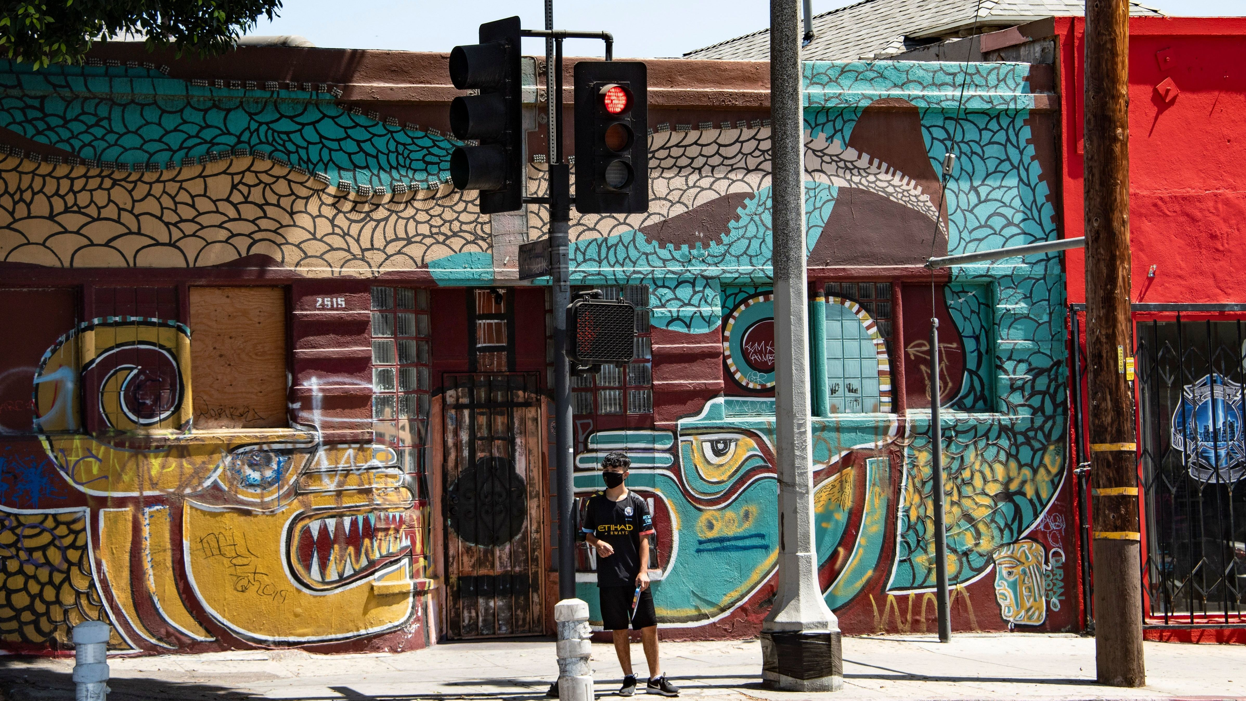 A man waits to cross the street in the largely Latino neighborhood of East Los Angeles on Aug. 7. California has implemented a new health equity metric to help address the outsize effect of coronavirus on the state's communities of color.