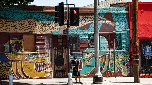 A man waits to cross the street in the largely Latino neighborhood of East Los Angeles on Aug. 7. California has implemented a new health equity metric to help address the outsize effect of coronavirus on the state