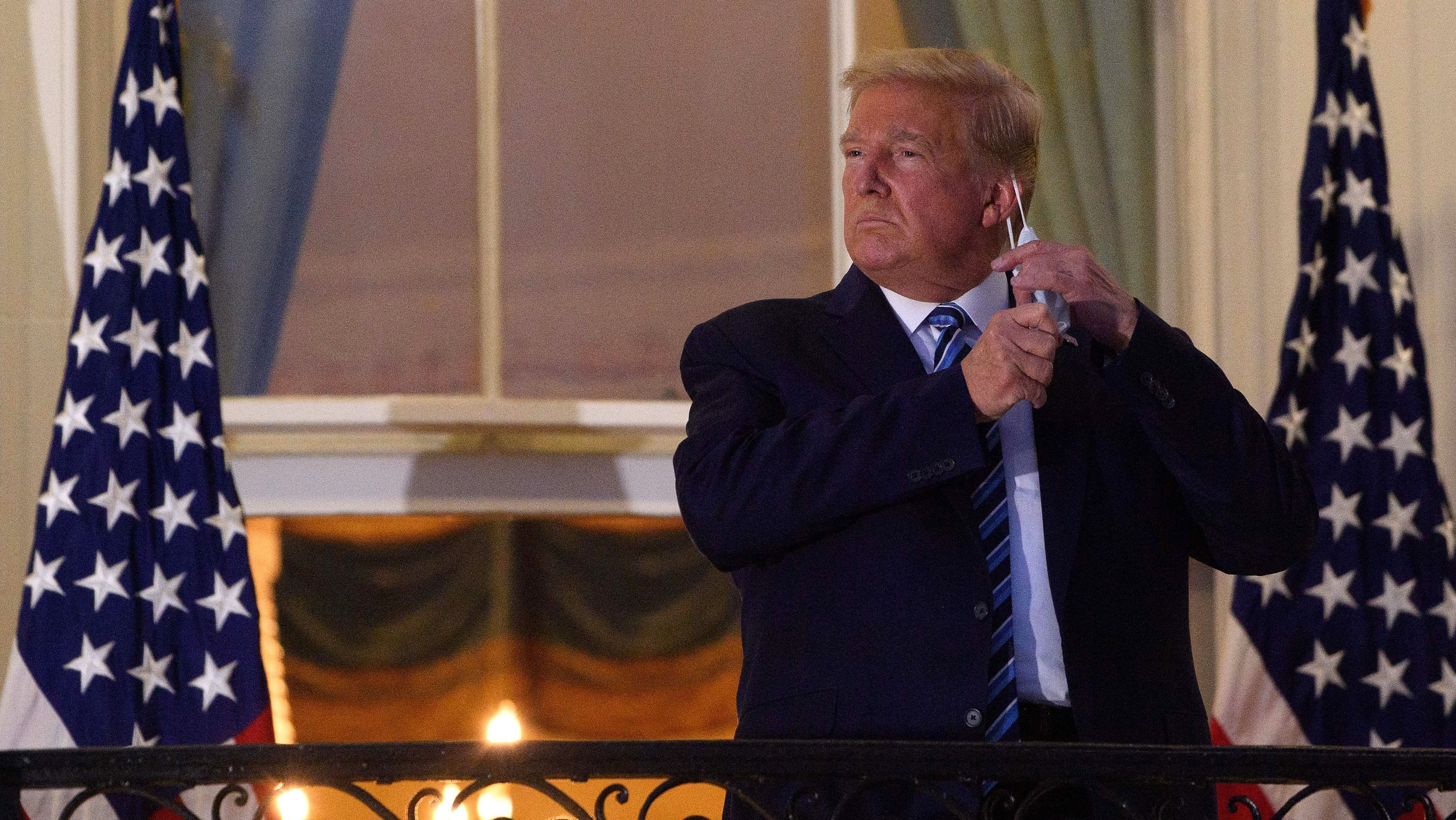 President Trump takes off his face mask Monday night as he arrives at the White House upon his return from Walter Reed National Military Medical Center.
