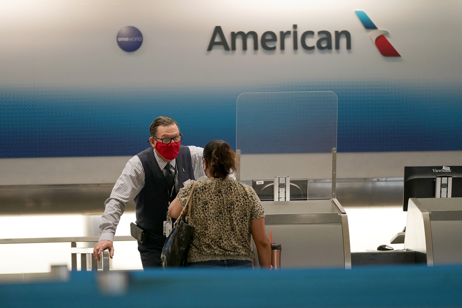 American Airlines ticket agent Henry Gemdron, left, works with a customer at Miami International Airport on Sept. 30. Travel industry groups warn of huge job losses if Congress and the White House fail to reach agreement on coronavirus relief soon. (Lynne Sladky/AP)
