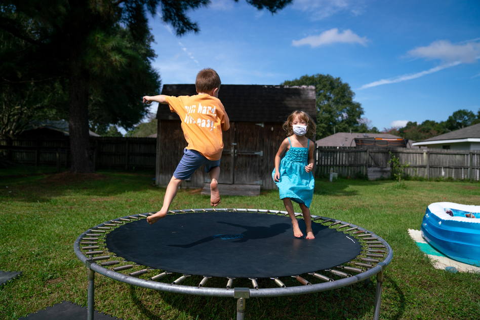 Lachlan (left) and Lillian Barilleau play in the backyard of their home in Central, La. They were displaced from the house for months after a flood in 2016. (Ryan Kellman/NPR)