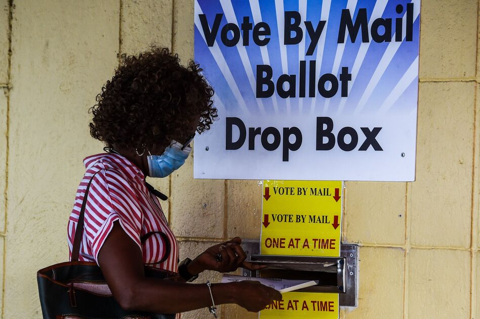 A woman drops her ballot by mail at Broward County Supervisor Of Elections Office in Lauderhill, Fla., on Monday. (Chandan Khanna/AFP via Getty Images)