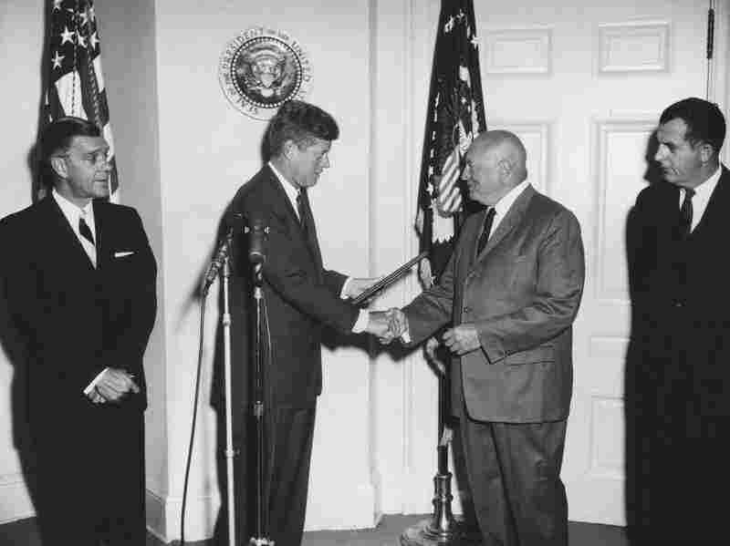 President John F. Kennedy shakes hands with former Commissioner of Narcotics, Harry J. Anslinger, upon presenting him with an outstanding record citation.