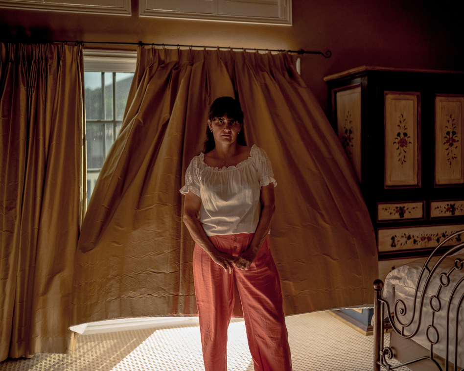 """After making a new life in the U.S., Jacob Moscovitch's mother, or Imma, raised three kids and led the household while working a part-time job. Moscovitch says his older sister Simone told him, """"Imma is my superhero, no cape necessary."""" Here, Imma stands for a portrait in her bedroom on May 8. (Jacob Moscovitch)"""