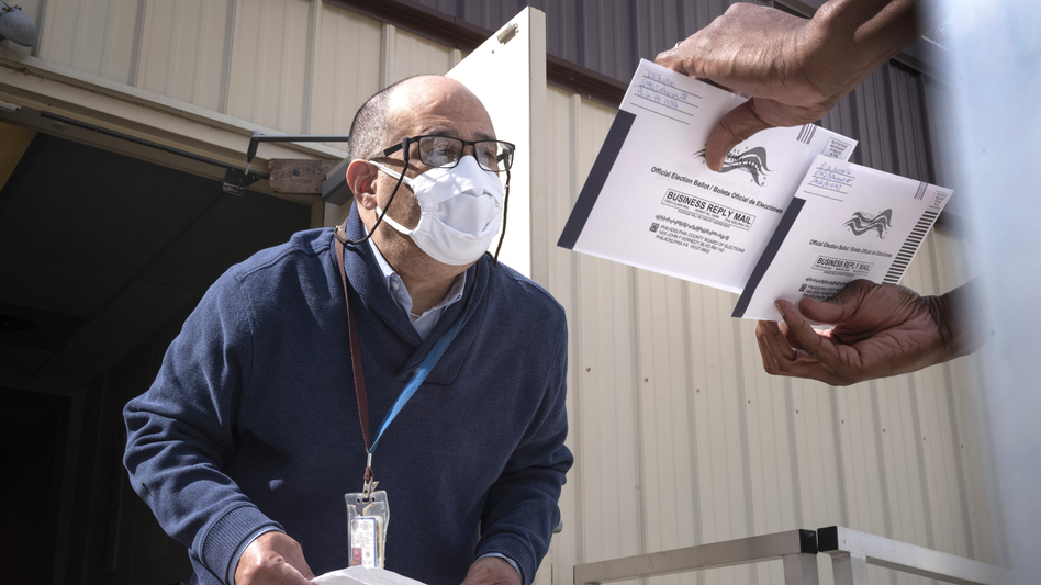 An employee of the Philadelphia City Commissioners Office examines ballot envelopes at a satellite election office at Overbrook High School in Philadelphia. Local election clerks can't start verifying mailed-in ballots in Pennsylvania until Election Day and in Michigan until the day before. (Laurence Kesterson/AP)