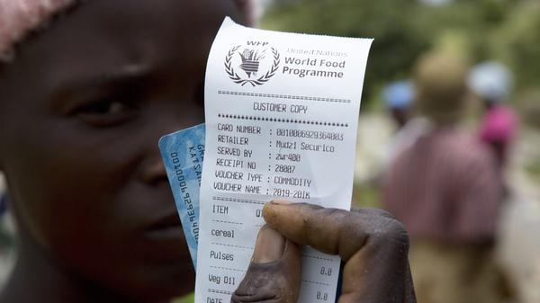 Una mujer sostiene un vale antes de recibir ayuda alimentaria en Mudzi, Zimbabwe, en febrero.  El viernes, el Programa Mundial de Alimentos de las Naciones Unidas recibió el Premio Nobel de la Paz 2020.
