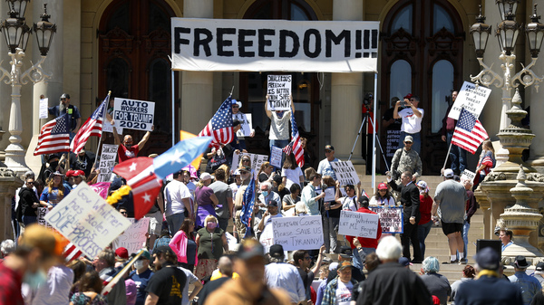 People protest at the Capitol during a rally in Lansing, Mich., Wednesday, May 20, against Gov. Gretchen Whitmer