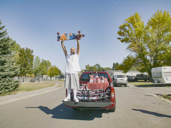 """Nathan Apodaca's TikTok video, in which he longboards to Fleetwood Mac's """"Dreams,"""" has catapulted him to viral fame. Here, he is standing in the pickup truck given to him by Ocean Spray. In his video, Apodaca sips from a bottle of Ocean Spray's Cran-Raspberry juice."""