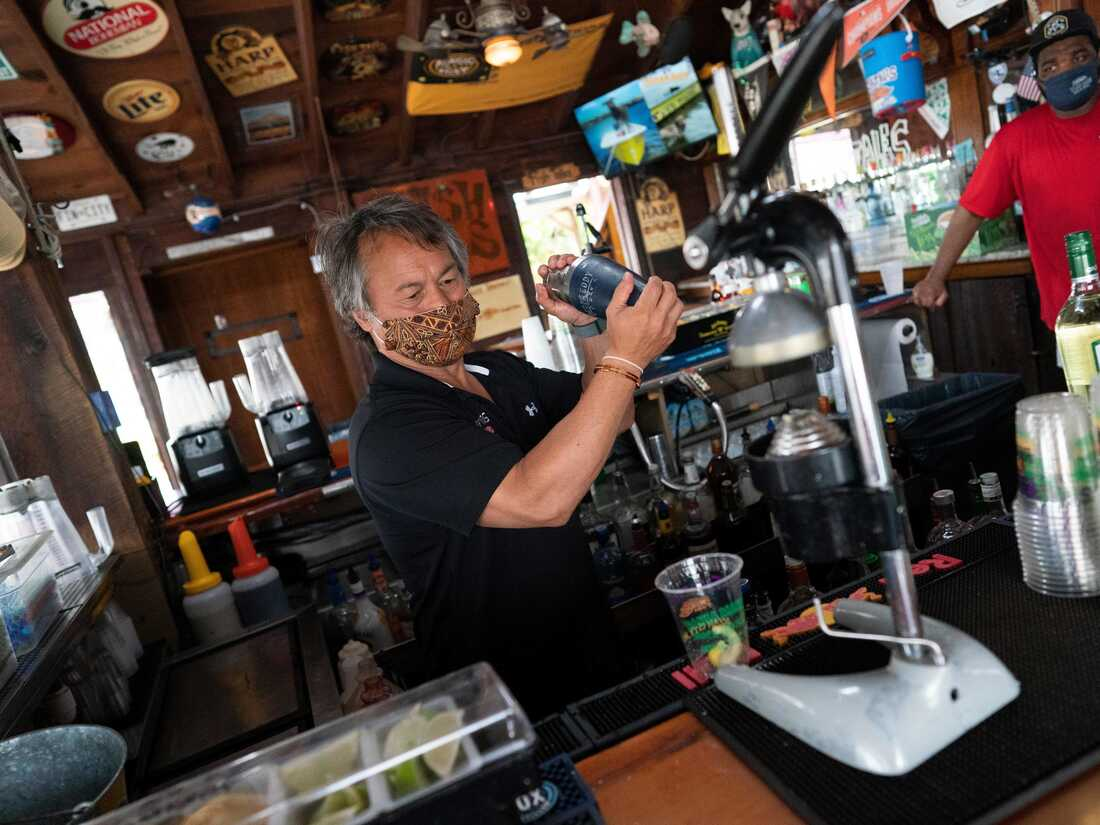 A bartender wearing a facemask makes drinks as Fish Tails bar and grill opens for in person dining, amid the coronavirus pandemic- (Photo by Alex Edelman / AFP) (Photo by ALEX EDELMAN/AFP via Getty Images)