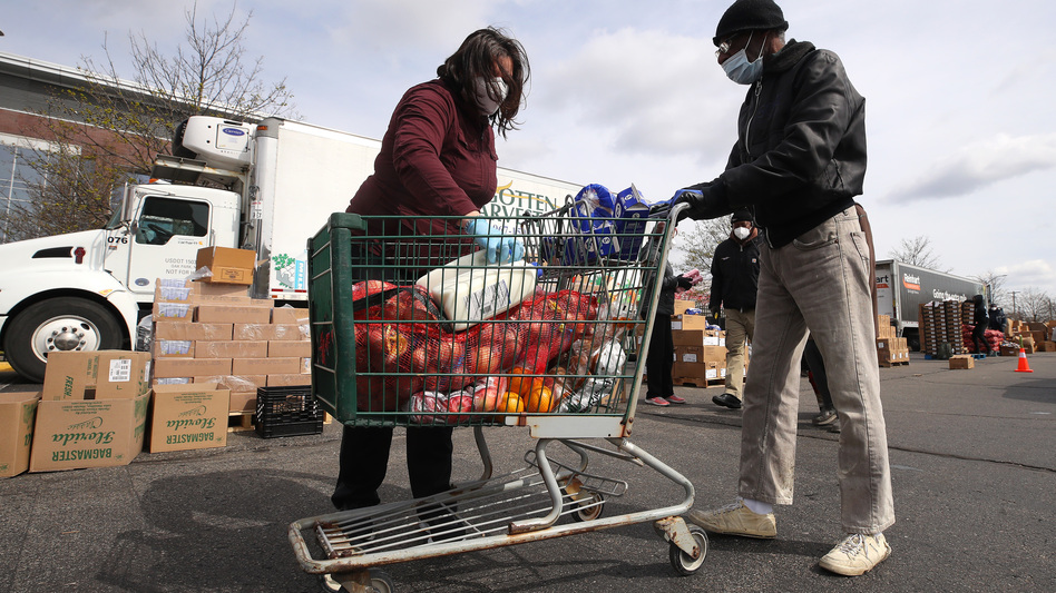A volunteer loads food into a cart at a mobile pantry in Detroit in April 2020. The COVID-19 pandemic has led to an uptick in the demand at food banks. (Gregory Shamus/Getty Images)