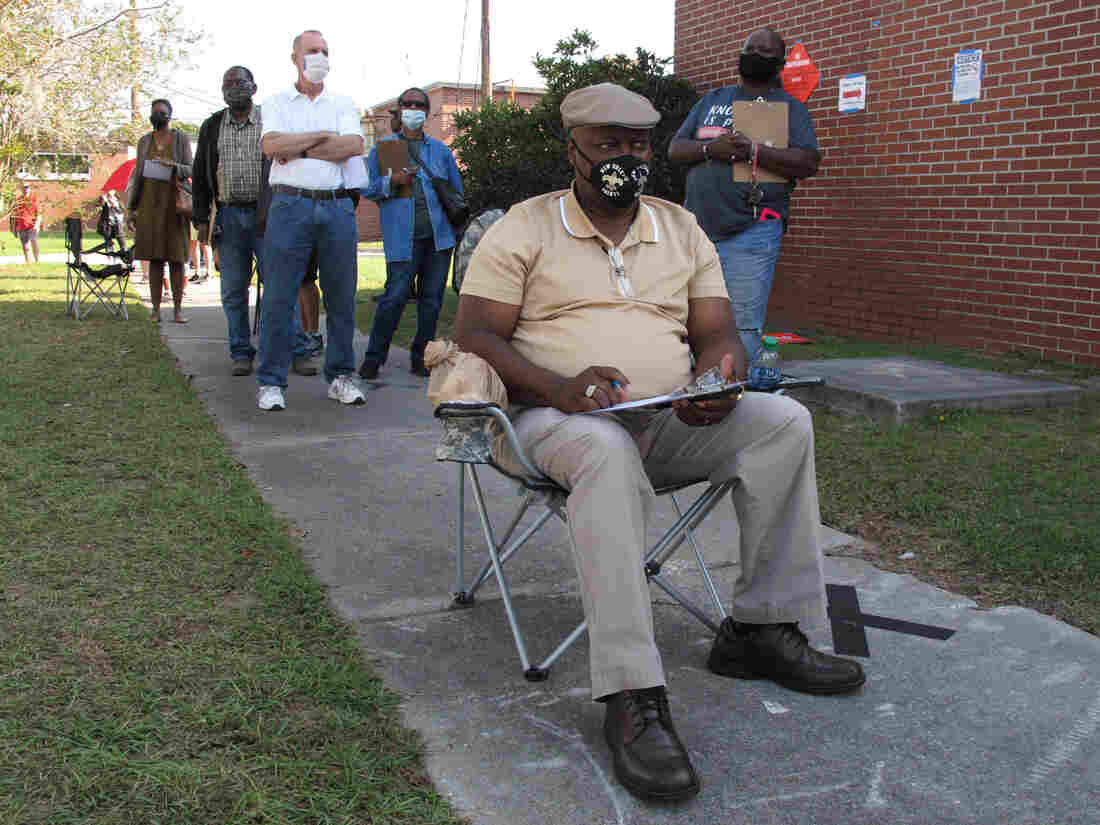 Richard Williams sits in a folding chair, filling out paperwork, as he waits in line to vote early in Savannah, Ga., on Wednesday. Black people are going to the polls by the thousands and waiting in lines for hours to vote early in Georgia.