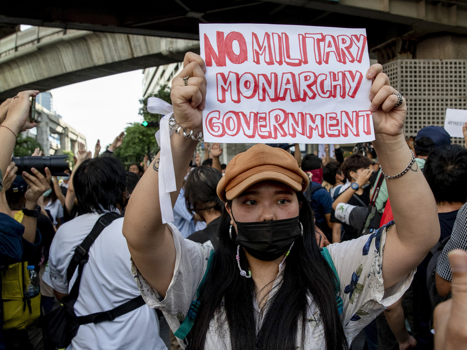 A pro-democracy protester displays a sign during a demonstration Thursday in the central business district of Bangkok.