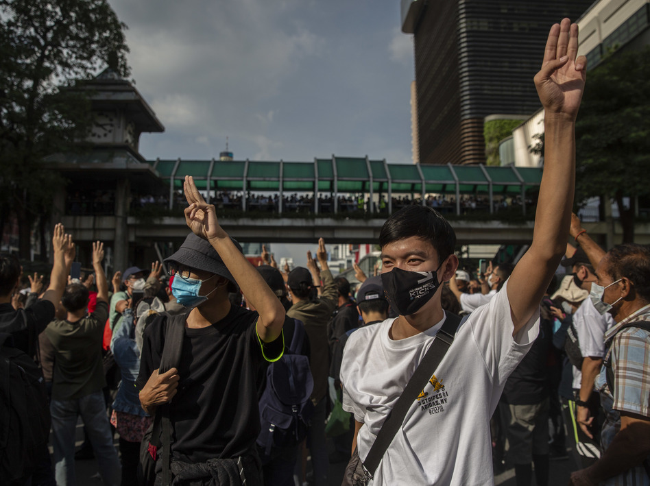 Pro-democracy protesters hold up a three-fingered salute Thursday at Bangkok's Ratchaprasong intersection.