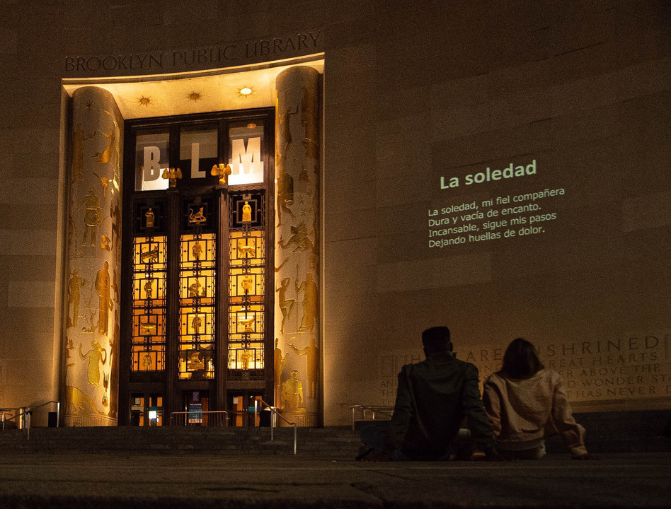 A poem projected onto the Brooklyn Public Library.