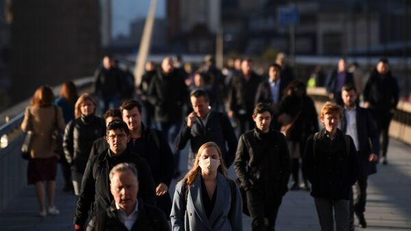 Commuters walk over London Bridge toward the City of London during the morning rush hour on Thursday. The city and other large areas are now under a high alert for the coronavirus, as health officials enact new restrictions.