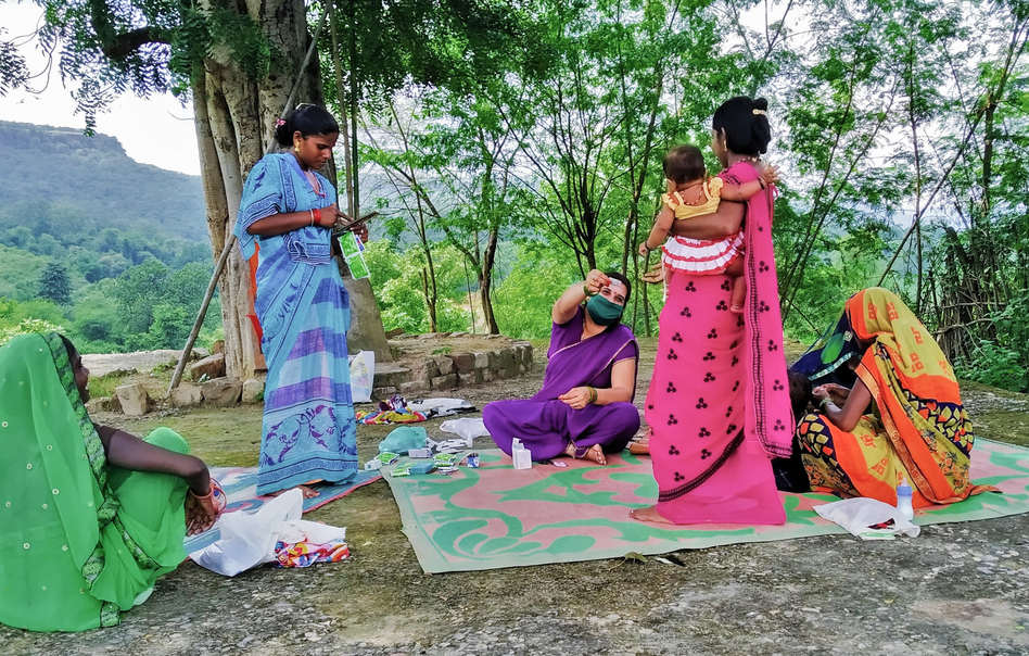 Dwivedi, in purple sari, shares health information with women in the village. COVID-19 is a hot topic.