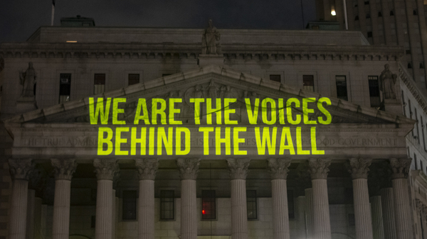 """""""The Writing On The Wall"""" art installation projects writings by incarcerated people onto the sides of buildings, such as The New York State Supreme Court Building, above."""