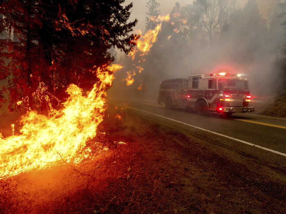 A firetruck drives along state Highway 168 last month while battling the Creek Fire in the Shaver Lake community of Fresno County, Calif. (Noah Berger/AP)