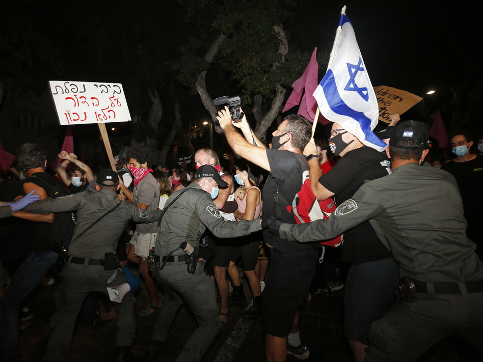 Israeli police scuffle with protesters during a demonstration against Prime Minister Benjamin Netanyahu in Tel Aviv on Oct. 6. Protests continued despite a government ban on large public gatherings, including protests against Netanyahu. The sign reads: