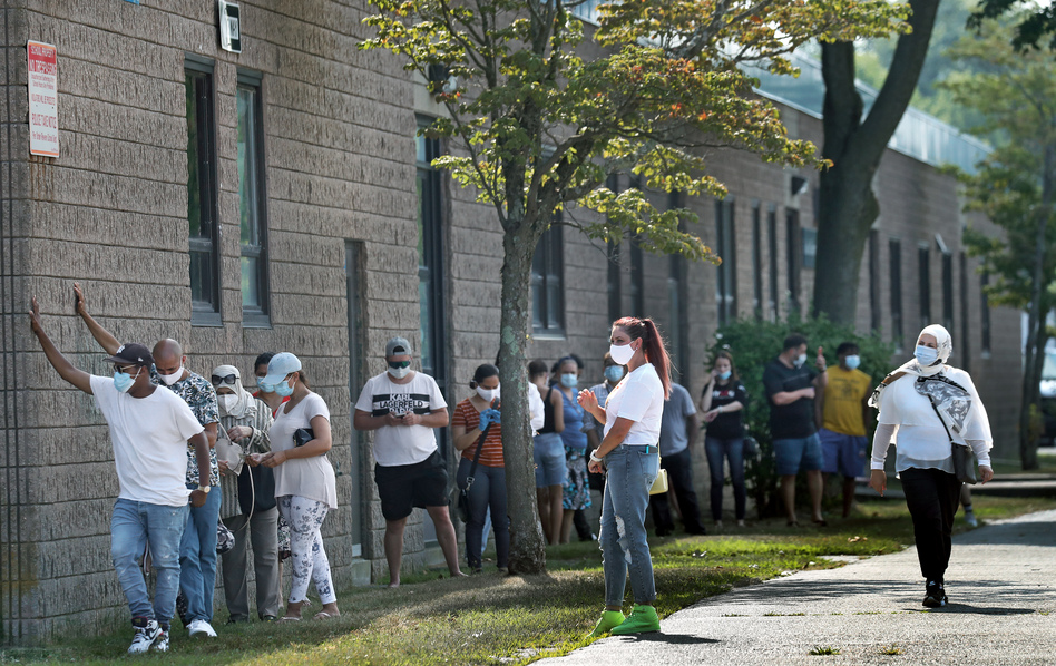 People wait in the shade while in line to get coronavirus tests in Revere, Mass. ( David L. Ryan/Boston Globe via Getty Images)
