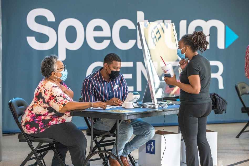 Poll workers assist a voter at the Spectrum Center in Charlotte, N.C., during the first day of early voting there on Thursday.