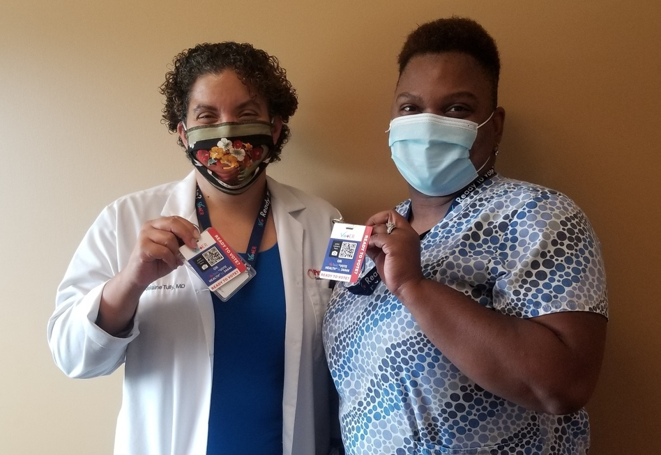 Dr. Madelaine Tully, left, and medical assistant Marshae Love hold up their VotER badges at Progressive Community Health Center in Milwaukee. VotER is an initiative to register new voters at ERs and clinics.