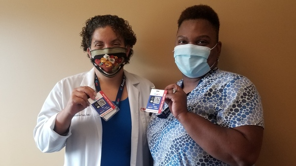 Dr. Madelaine Tully and medical assistant Marshae Love hold up their VotER badges at Progressive Community Health Center in Milwaukee. VotER is an initiative to register new voters at ERs and clinics.