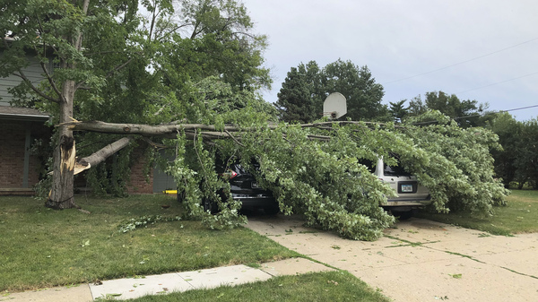 A tree fell across vehicles at a home in West Des Moines after a severe thunderstorm moved across Iowa on Aug. 10. It was the costliest storm system in modern U.S. history.