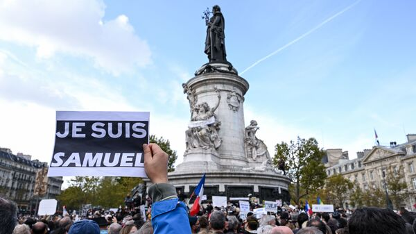 """Demonstrators like the one shown here carried """"I am Samuel"""" signs as they gathered on Place de la République in Paris on Sunday to pay tribute to slain history teacher Samuel Paty. Similar gatherings took place in several other cities as France reels from the attack."""