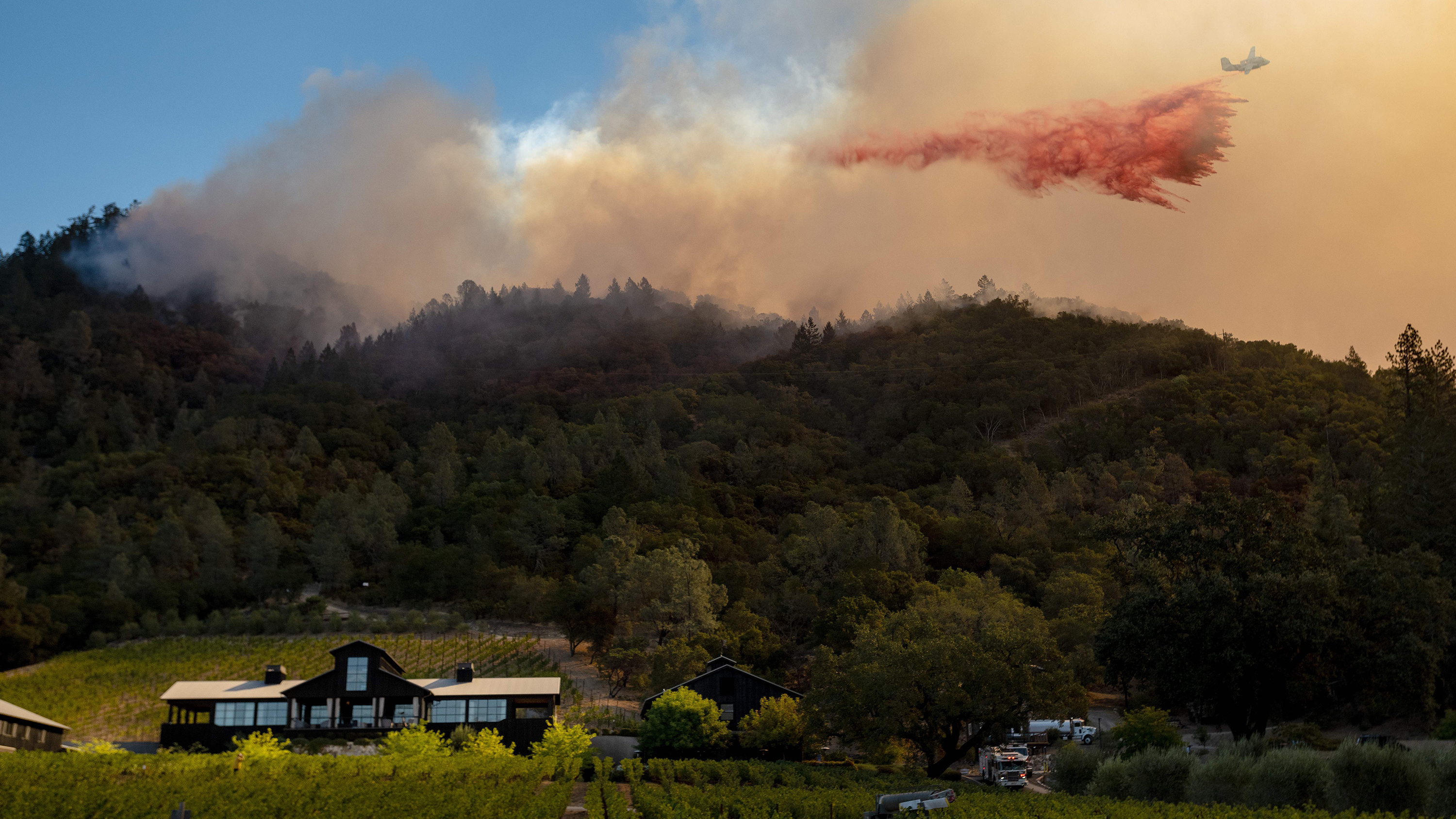 A California Department of Forestry and Fire Protection airplane drops fire retardant along a burning hill during the Glass Fire in Calistoga, Calif., in September. California is one of two states to require wildfire risk be disclosed to new homebuyers.