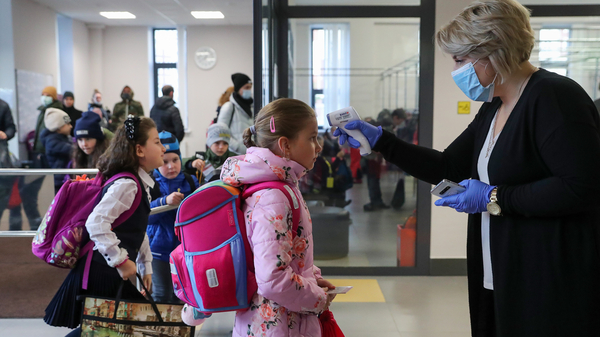 More than 40 million coronavirus infections have now been reported worldwide. Here, a staff member at a school in Moscow uses an infrared thermometer on Monday to screen students. Moscow schools reopened after a two-week fall holiday, but a rise in cases means only primary school pupils will be in classrooms.
