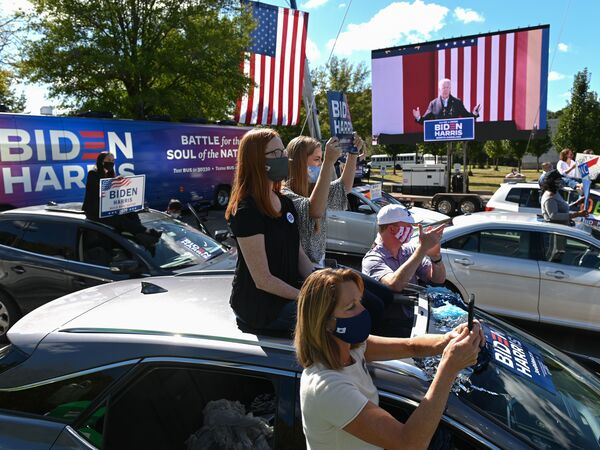 Supporters of Democratic presidential nominee Joe Biden sit atop their vehicles as they listen to him speak Sunday at Riverside High School in Durham, N.C.
