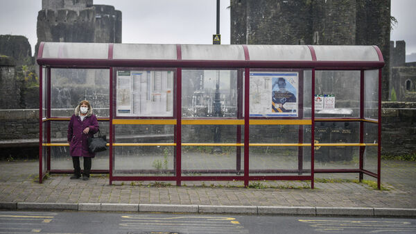A woman wears a face mask as she waits for a bus last month in South Wales. Wales is imposing a lockdown amid a surge in cases.
