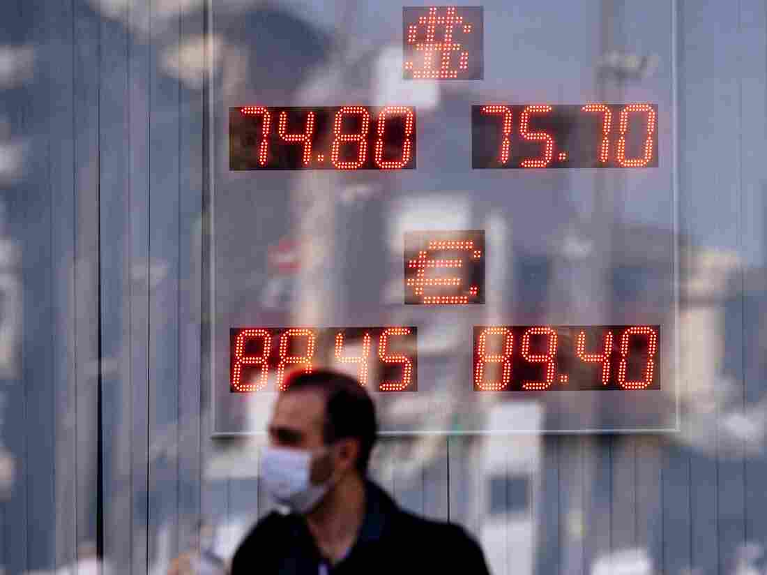 A man wearing a face mask passes by a screen displaying the currency exchange rate of the Russian ruble with U.S. dollar and Euro, September 2020.