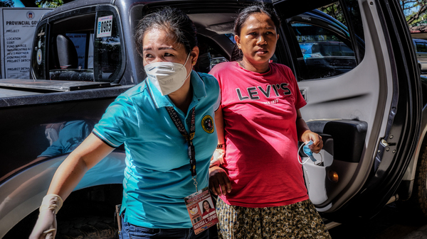 Marissa Tuping, a rural midwife, and Risa Calibuso, right, arrive in Nueva Vizcaya Provincial Hospital on July 21. Calibuso gave birth to her son moments later.