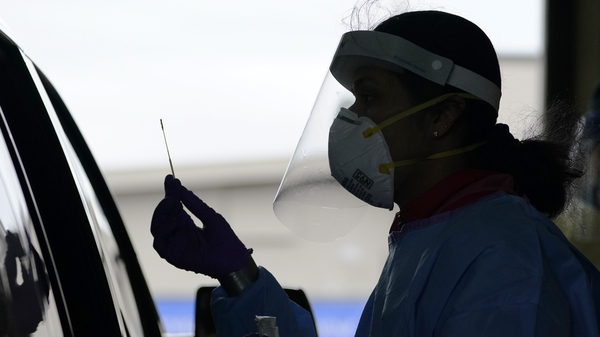 A University of Washington research coordinator holds up a swab after testing a someone for coronavirus on Oct. 23 in Seattle. The U.S. recorded a record high number of new daily cases Friday.