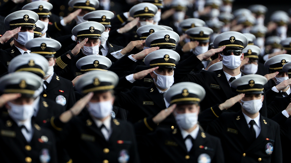 Midshipmen wearing face masks stand and salute before the Navy Midshipmen play against the Houston Cougars on Saturday in Annapolis, Md. Researchers have tried to estimate how many lives would be saved by universal mask-wearing. (Patrick Smith/Getty Images)