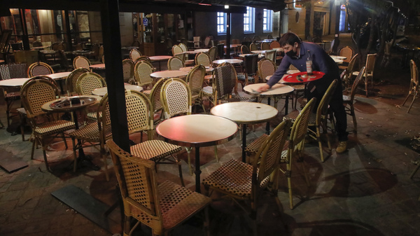A waiter cleans a table after closing in Saint Germain-en-Laye, west of Paris on Oct. 16,  to comply with new COVID-19 restrictions forcing restaurants, cinemas and theaters in the French capital to close. France imposed a nighttime curfew in Paris and other major cities to curb the spread of the coronavirus.